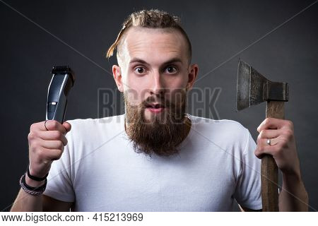 Young Handsome Bearded Man Holding An Ax And Trimmer In His Hands