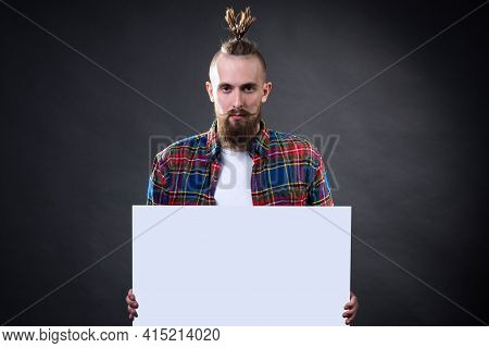 A Young Man With A Bushy Beard And A Stylish Haircut Holds An Empty Letterhead In The Studio. Copysp