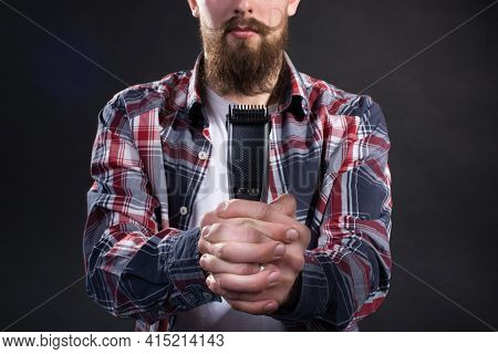 A Young Handsome Man With A Thick Beard And A Large Mustache In A Plaid Shirt Holds A Shaving Trimer
