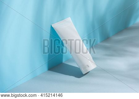 White Plastic Tube With Face, Hand And Body Cream On Gray-blue Paper. Sun Protection Lotion, Sunscre