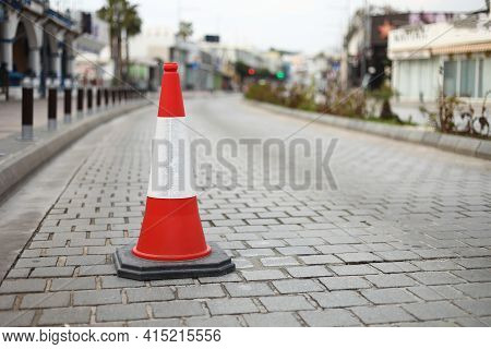 Cone Sign On The Road. Striped Orange Cones On The Asphalt Road. Plastic Orange Cone On The Road.tra