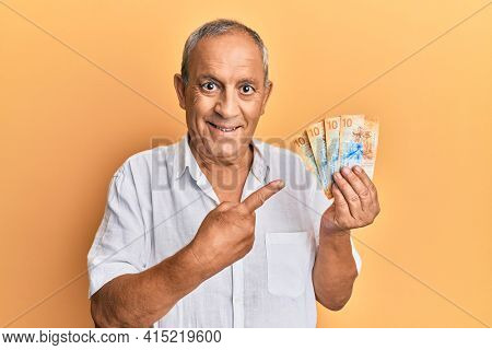 Handsome mature man holding swiss franc banknotes smiling happy pointing with hand and finger