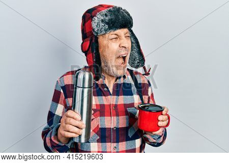 Handsome mature handyman wearing winter hat with ear flaps drinking hot coffee from thermo angry and mad screaming frustrated and furious, shouting with anger. rage and aggressive concept.