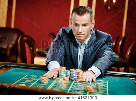 Gambler placing a bet at the roulette table at the casino. Risky entertainment of gambling