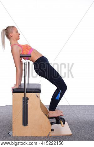 A 20-year-old Trainer Practices Pilates On An Elevator Chair, Bending Into A Bridge Position.