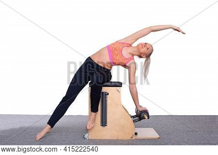 A 20-year-old Trainer Practices Pilates On An Elevator Chair, Arching Her Body. She Sits In A Light