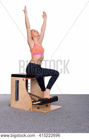 A 20-year-old Trainer Practices Pilates On An Elevator Chair, Raising Her Arms High Above Her Head.