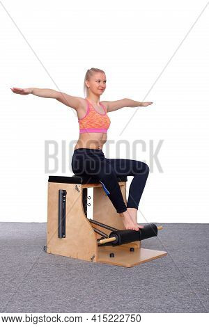 A 20-year-old Trainer Practices Pilates On An Elevator Chair, Raising Her Arms To Shoulder Height An