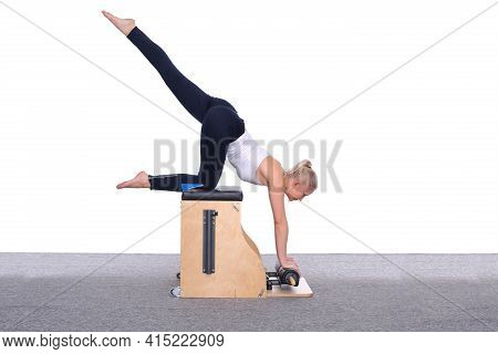 A 20-year-old Female Trainer Practices Pilates On An Elevator Chair, Lifting Her Leg High Above Her