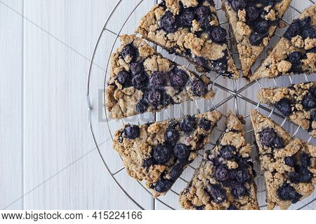Freshly Baked Oat Blueberry Scones On Cooling Rack On White Wooden Background, Top View, Flat Lay. V