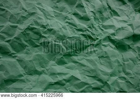 Top View Photo Of Crumpled Craft Paper. Emerald Color Paper Background With Copyspace. Vintage Paper
