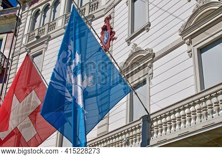 Close Up Of The Flags Of City Locarno And Switzerland Hanging In Front Of The Municipio Di Locarno B