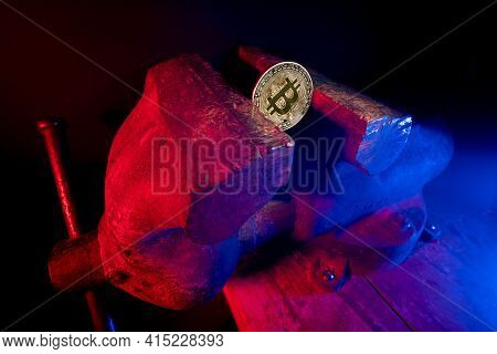 Bitcoin Mounted In A Steel Vise In Red And Blue Light. Keeping Bitcoin Safe In Crypto Wallet. Pressu