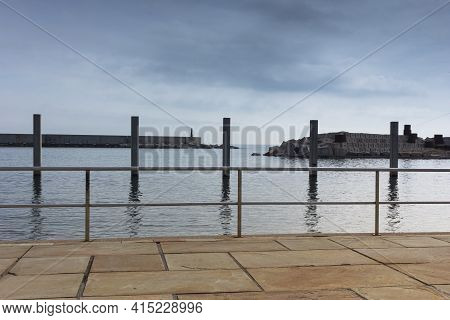 Saltwater Pool In The Mediterranean Sea, In Winter, Without Waves And A Cloudy Blue Sky. November In