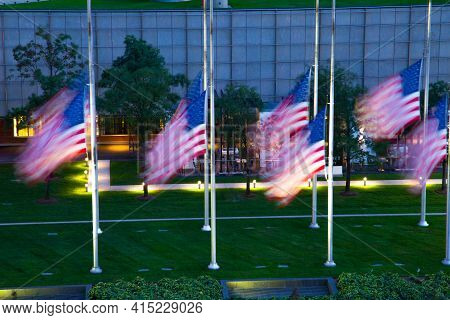 Motion Blurred American Flags At Half Mast Blowing In The Wind In Front Of A Downtown Detroit Buildi