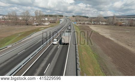 Top View Of Trucks Driving On Motorway In Spring. Shot. Follow Trucks And Cars Driving Along Country
