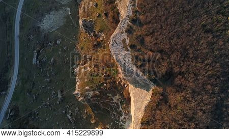 Top View Of Rocky Cliff Line. Shot. Rocky Cliff Is Illuminated By Suns Rays On Background Of Dark Pl