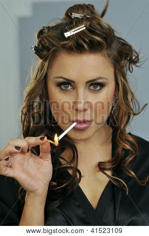 Portrait of pretty young smoking woman during makeup and hairstyling process