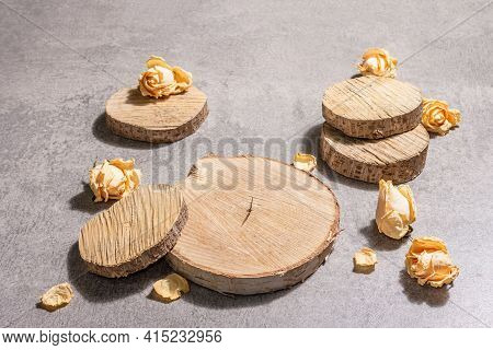 Modern Set Of Wooden Stand Podiums With Dry Roses Flowers On Grey Stone Concrete Background