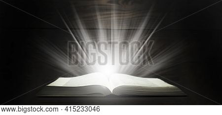 Open Bible. Rays Of Light Come Down From The Book. The Holy Book. On A Wooden Table
