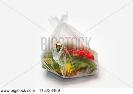 Defocus. Plastic Plant. Red And Green Plants Flowers In A Plastic Bag On A White Background. A Dry B