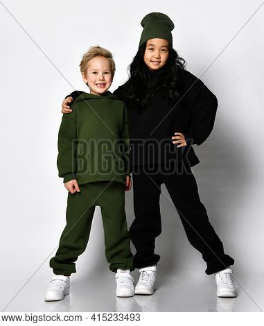 Full Length Studio Portrait Of Little European Boy And Asian Teenage Girl Model In Warm Fashion Spor