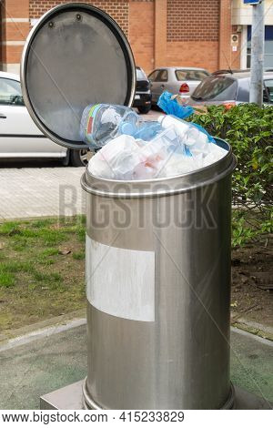 Full Metal Garbage Container With Plastic Rubbish On A City Street. Municipal Stationary Waste Colle