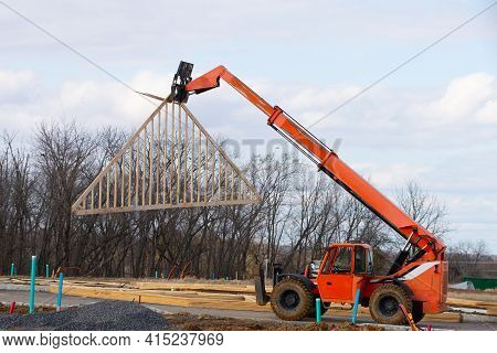The Rafters Are Lifted By A Construction Loader Side Frame