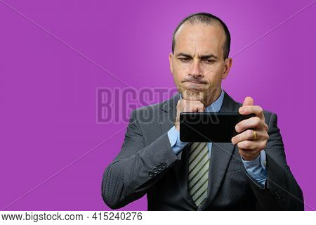 Mature Man With Suit And Tie, Looking At His Smartphone, Disappointed And With His Fist Under Chin.