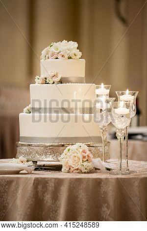 Wedding Ceremony Three Tiered Cake Made With White Frosting And Grey Trim Decorated With White And P