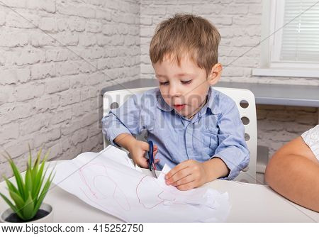 Cute Small Boy Sitting At The Table. Little Happy Boy Play With Paper. Craft For Children. Artwork W