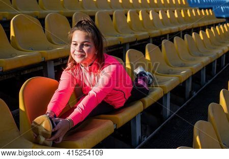 Athletic Fit Flexible Girl Child Do Splits Leg Stretch Gymnastic Training On Stadium Seats, Gymnast