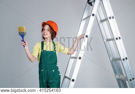 Teen Girl Laborer In Protective Helmet And Uniform On Ladder With Painting Brush, Renovation