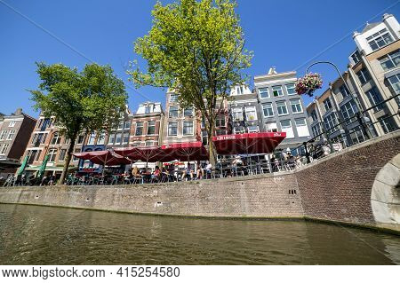 Amsterdam, Netherlands - July 03, 2018: People Relax On The Embankment Of Amsterdam