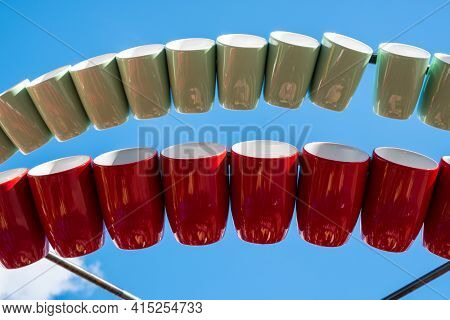 Row Of Colorful Mugs Store And Hanging On A 'mug Tree', A Wooden Or Metal Pole Mounted On A Round Ba