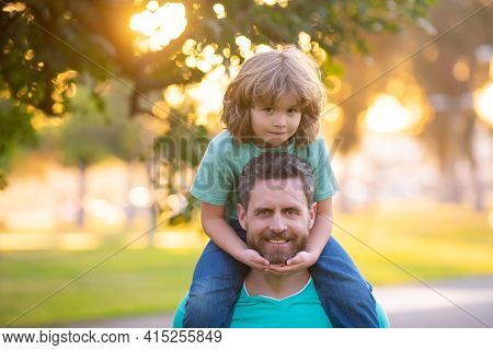 Father Giving Son Ride On Back In Park. Portrait Of Happy Father Giving Son Piggyback Ride On Should