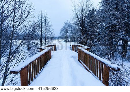 Snow Covered Log Cabins In The Woods In A Forest.