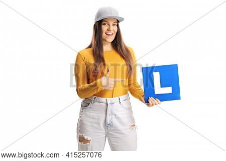 Young female driver holding a learner plate isolated on white background