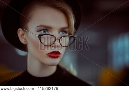 Beauty, fashion concept. Close-up portrait of a fashionable young woman in modern glasses and hat in interiors. Optics, eyewear.