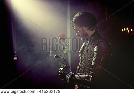 The noble knight in armor knelt down and holds out the rose in his hands looking down in the castle. Romance.