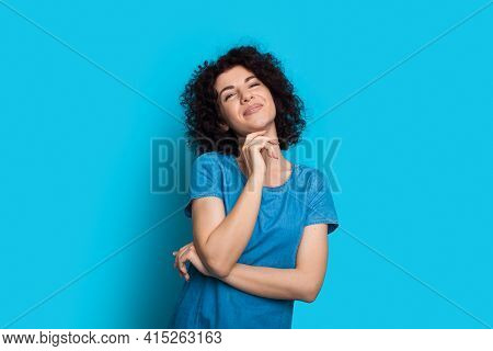 Adorable Curly Haired Woman Is Touching Her Chin Smiling At Camera On Blue Studio Wall