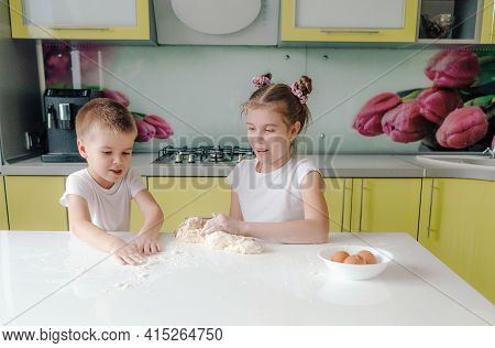Beautiful Young Brother And Sister Messing Around With Dough In The Kitchen While Cooking. Young Mot