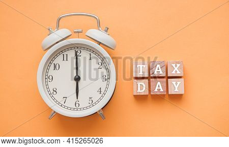 White Alarm Clock And Tax Day Words In Wooden Letterpress Printing Blocks On Yellow Background.