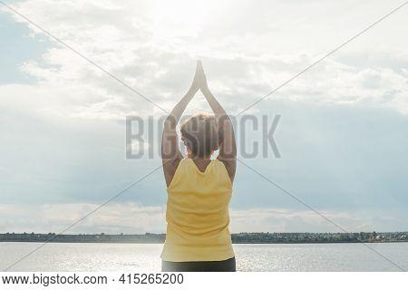 Woman Making Yoga Near River. Back View.