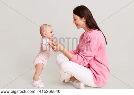 Profile Of Dark Haired Female Wearing Casual Pink Sweatshirt And Pants Sitting On Floor With Cross L