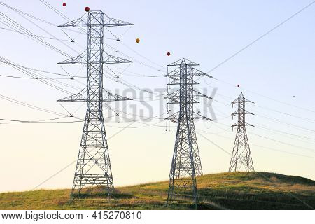 Electric Pylons Holding Wires Transporting Power From An Energy Source To The Urban City On A Lush H
