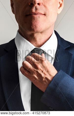 Businessman wearing tie, getting ready to work