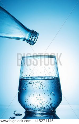 A Glass Of Highly Carbonated Water From A Bottle In Bright Blue Light