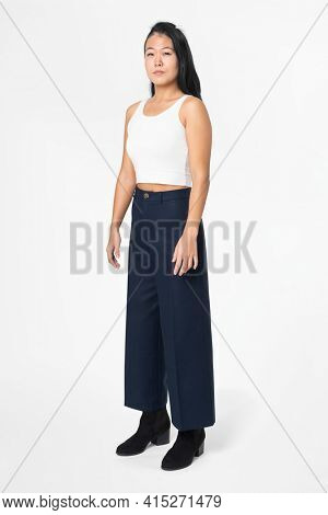 Cool woman in white tank top and black a-line pants street fashion full body