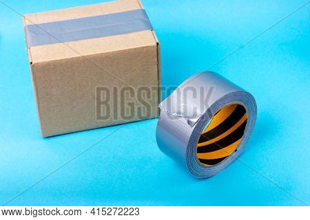 Cardboard Box Sealed With Adhesive Tape And Gray Adhesive Tape. Packing Parcels With Adhesive Tape.